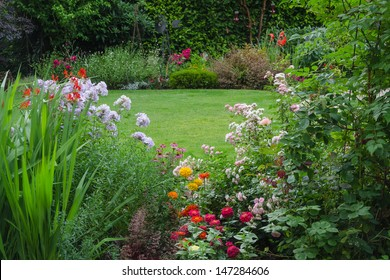 View of a lush backyard lawn surrounded by colorful flowers.
