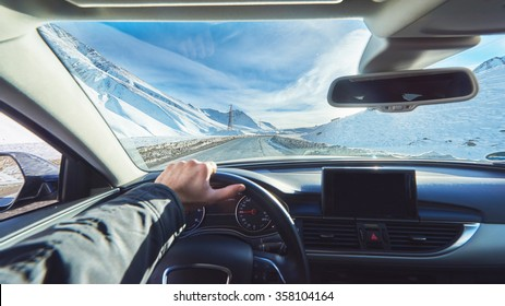 view from luxury car inside with part of interior gps screen with driver male hand on  the steering wheel during bright snowy sunny day on straight ice road with snowy mountains in background