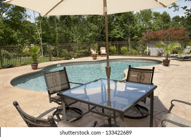 A view of a luxury salt water pool and patio in a residential backyard through patio furniture.