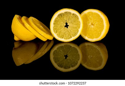 View of macro still life - cuted lemon on black background with reflection