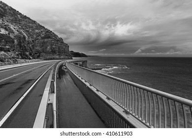 View of the magestic Sea Cliff Bridge and surrounding landscape of Grand Pacific Drive, Sydney, Australia. Black and white image.
