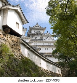 View of the main tower of Himeji Castle in the distance between one of the lower walls  and trees of the castle grounds during the daytime