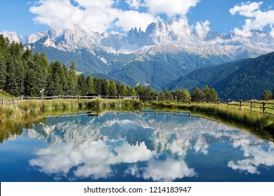 view of the majestic Catinaccio Rosengarten in the Italian Dolomites Southtyrol . reflection in a small lake