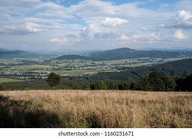 view from Mala Kycera hill in Moravskoslezske Beskydy mountains in Czech republic with rural scene with villages, meadows and fields with hills of Silesian Beskids and Jablunkovske mezihori mountains