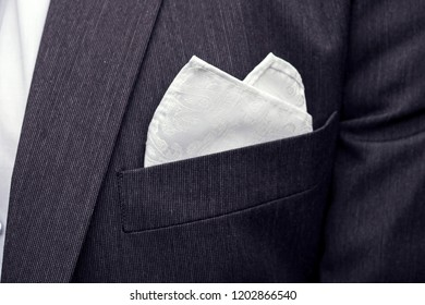 View to the male coat pocket with a fixed white square. Men's suit accessories. Wedding male guest's attire. Male wedding style. Formal dinner outfit for men. Elements of a suit. Pocket square folding