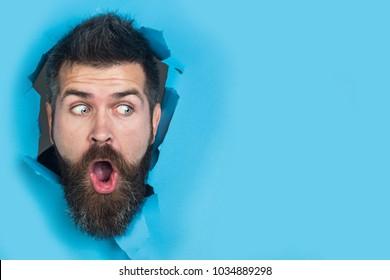 Blick auf männliches Gesicht durch Loch in blauem Papier. Überraschender Bartmann, der Loch in Papier macht. Kopieren Sie Platz für Werbung, um Text oder Slogan einzufügen. Rabatt, Verkauf, Saisonverkauf.