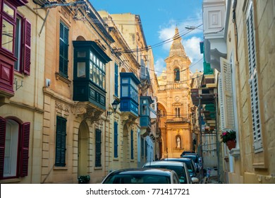 view of maltese narrow streets with balconies and cathedral in Sliema city in day, Malta