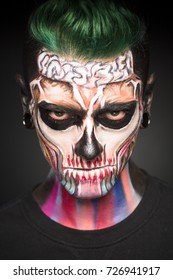 View of man with green hair and Halloween makeup. Mystical face art, man with colored dead face skull mask.