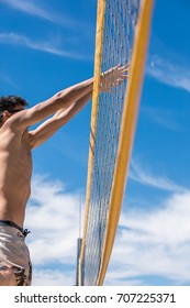 View of the man jumping by the volleyball net while playing volleyball