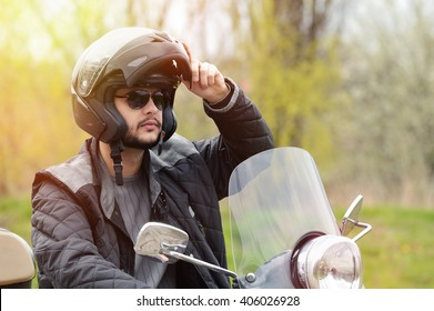 View of a man on the motorcycle with a helmet on.Lens flare
