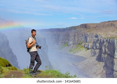 View of man photographer standing near famous Dettifoss waterfall in Vatnajokull National Park, Northeast Iceland