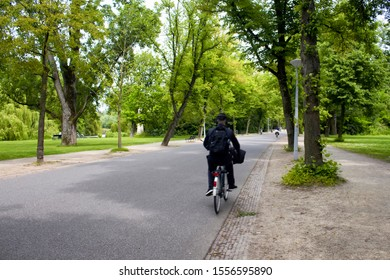 View of man riding bicycle in blurry motion, trees and road at Vondelpark in Amsterdam. It is a public urban park of 47 hectares. It is a summer day.