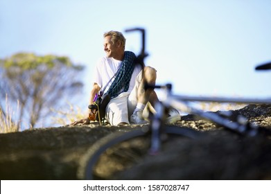 View of a man sitting on the ground with a bicycle in the foreground