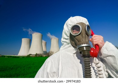 A view of a man wearing a breathing mask and a hazmat suit, standing in front of a nuclear power station and talking on a red phone.