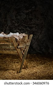 View of manger on straw covered floor in old barn