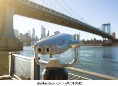 View of Manhattan bridge and New York City with a coin operated telescope binoculars viewer for tourists.
