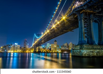 View of the Manhattan and Brooklyn Bridges and Downtown Brooklyn at night from Manhattan.