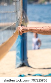 View of the man's hand touching the volleyball net