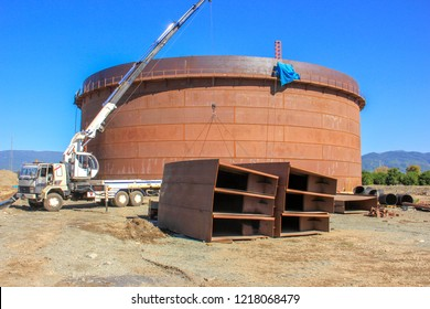 View of the manufacturing and assembly of the big crude oil storage tank with floating roof. The crane is lifting pontoons of the storage tank.