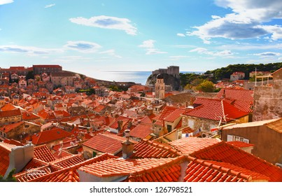 View of many landmarks of Old town in city of Dubrovnik, Croatia. Classic red tiled rooftops with fortified wall around the city