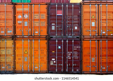 A view of many shipping containers doors while stacked on warehouse Useful for backgrounds or as design element.