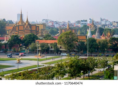 A view of the many spires, stupas and pagodas of Royal Palace in Phnom Penh, Cambodia, across the open space, trees and monuments of Wat Botum Park.