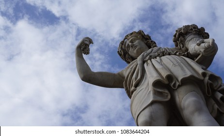view of marble statue with cornucopia from below with cloudy sky