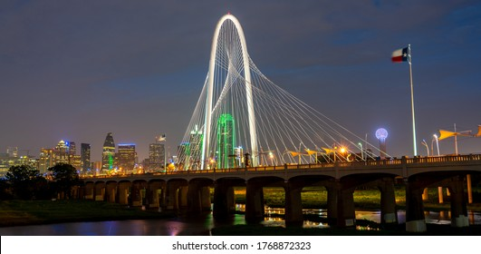 View of the Margaret Hunt Hill Bridge At Night With Texas Flag and Reunion Tower in the Background