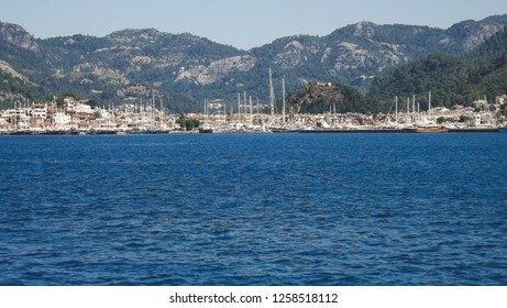 View of the Marmaris Cruise Port from the ferry coming from Rhodes Island. Marmaris Harbour with mountains on the background. Blue mediterranean sea and clear sky in a sunny day. TURKEY.