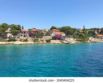 View of Maslinica with houses beside azure blue sea