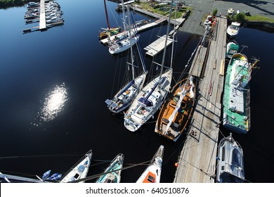 View from a mast top on the yachting marina during a regatta. Russia. Onega Lake. Sailboats  moored in the marina. The view from  the mast. Extreme sport ailing. Luxury boats