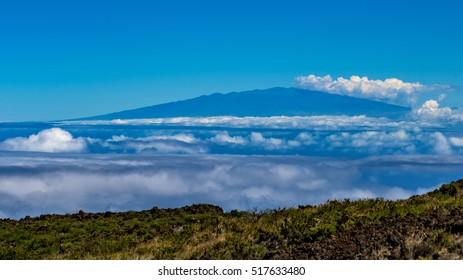 View of Mauna Kea volcano on the Big Island of Hawaii, seen from Haleakala volcano of Maui island