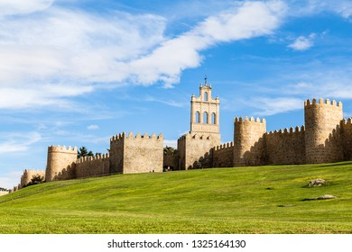 View of the medieval city walls surrounding the city of Avila, Spain, and the green lawn in front of Puerta del Carmen. Called the Town of Stones and Saints, Avila is a UNESCO World Heritage Site
