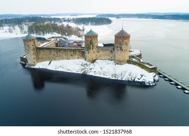 View of the medieval Olavinlinna fortress on Saimaa lake on a cloudy March day (aerial photography). Savonlinna, Finland