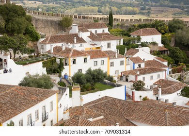 View of the medieval Portuguese village of Obidos. There is a Castle wall with battlements in the background