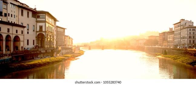 View of medieval stone bridge Ponte Santa Trinita  and Arno River from Ponte Vecchio bridge  in Florence, Tuscany, Italy at sunrise.