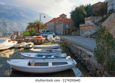 View of Mediterranean village with fishing boats in small harbor on sunny winter day. Montenegro, Bay of Kotor, Adriatic Sea, Muo village