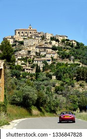View at Menerbes in the Luberon, France with a sports car on the road leading to the village
