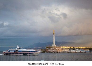 View of the Messina's port with the gold Madonna della Lettera statue during the storm with clouds, ships and sun light. Sicily, Messina, Italy.