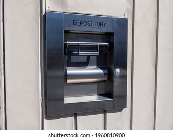 View of a metal depository box on the outside of a bank during daylight