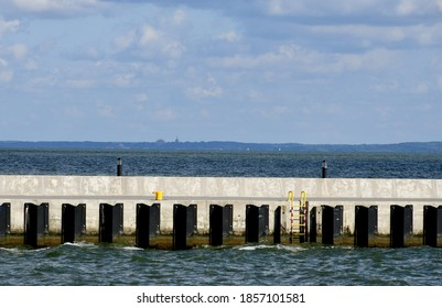 View of a metal pier, platform of marina with some wave protection modules and a yellow ladder seen next to the Polish sea with some land in the distance spotted on a sunny summer day in Poland