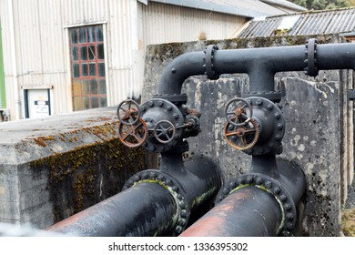 View of metal pipes and valves on an abandoned industrial site