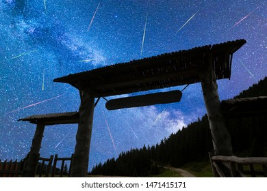 A view of a Meteor Shower and the blue Milky Way with wooden entrance door with a roof and fence silhouette in the foreground. Night sky nature summer landscape. Perseid Meteor Shower observation.