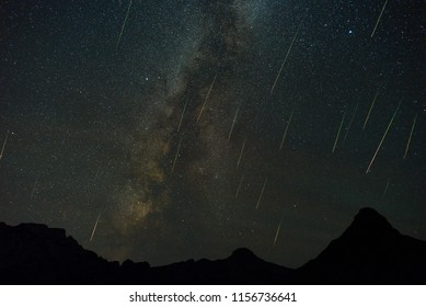 A view of a Meteor Shower and the Milky Way with mountains silhouette in the foreground.