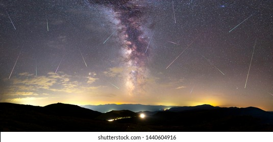 A view of a Meteor Shower and the Milky Way with an illuminated city silhouette in the foreground. Night sky nature summer landscape. Perseid Meteor Shower observation. Colorful shooting stars.