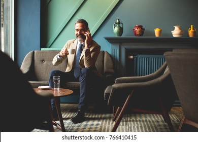 View at middle-aged businessman drinking coffee and using mobile phone in the loby