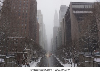 A view of Midtown Manhattan during a snow storm.  A fresh layer of snow  is coating the trees and sidewalks in New York City