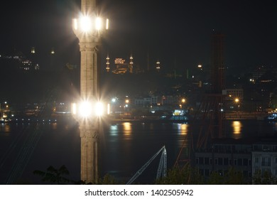 "View from the minaret with light to the Sultanahmet Camii with mahya (Text translation: ""Aid brings blessing."") and city lights with reflections on the sea. Istanbul, Turkey."