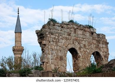View of minaret of Tekeli Mehmet Pasa Mosque next to ruins in Antalya Turkey