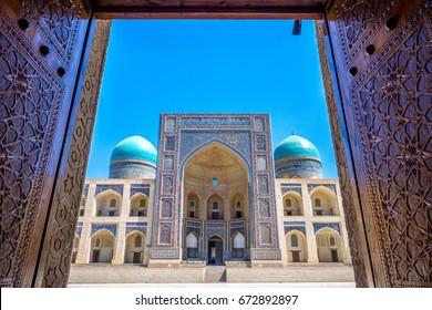 View to Mir i Arab madrassa thru the old wooden carved door, Bukhara, Uzbekistan